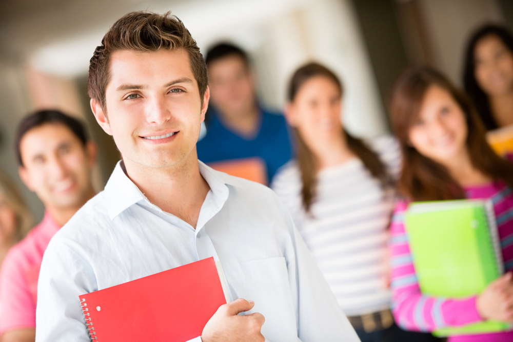 Group of college students smiling and holding notebooks